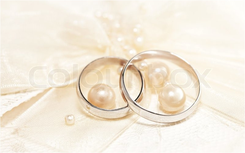 pair of golden wedding rings over invitation card decorated with silk bow pearls image 3141612